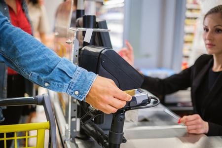 Mann, der in einem Lebensmittelgeschäft mit einem Smartphone bezahlt Standard-Bild