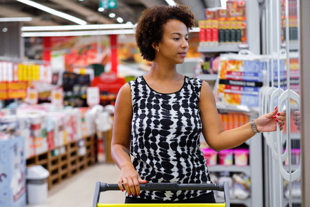 Pretty black woman choosing goods in a grocery store