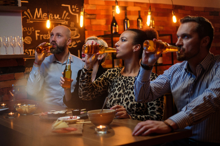 Group of friends watching tv in a cafe behind bar counter Standard-Bild