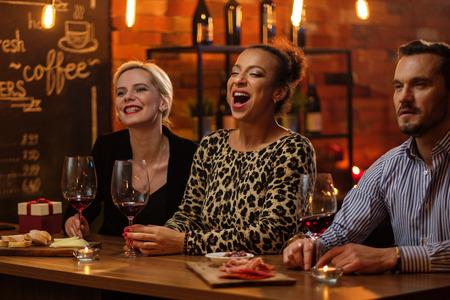 Groep vrienden met plezier praten achter de toog in een café