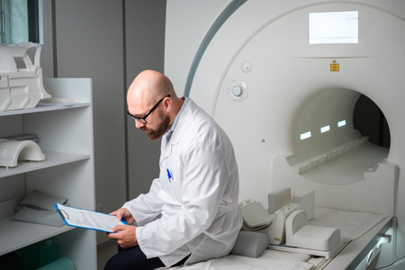 Doctor with a patient medical card near MRI scanner in a hospital Stock Photo