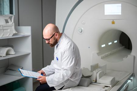 Médico con una tarjeta médica del paciente cerca del escáner de resonancia magnética en un hospital Foto de archivo