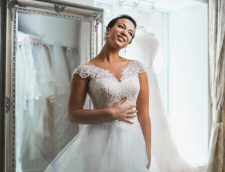 Beautifu novia eligiendo vestido de novia en un salón de bodas