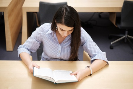 Young woman reading book in public library