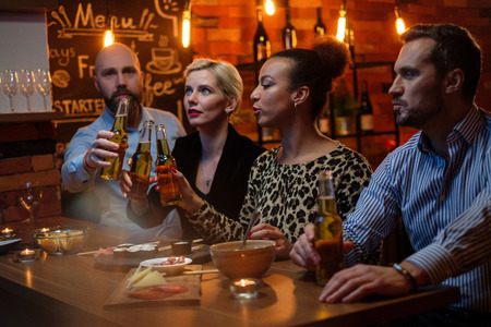 Group of friends watching tv in a cafe behind bar counter
