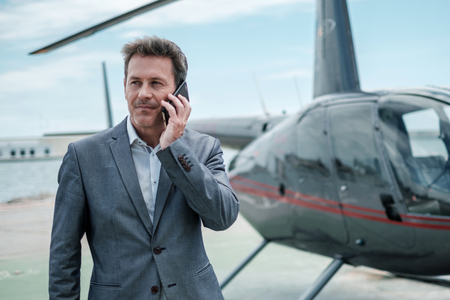 Businessman standing near private helicopter