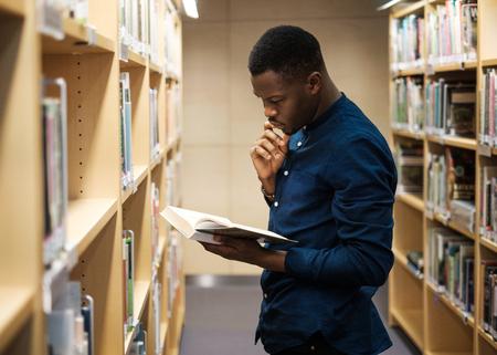 Joven negro eligiendo libro en biblioteca pública