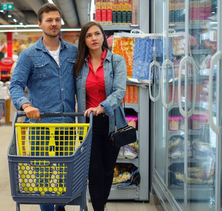 Couple choosing goods in a grocery store