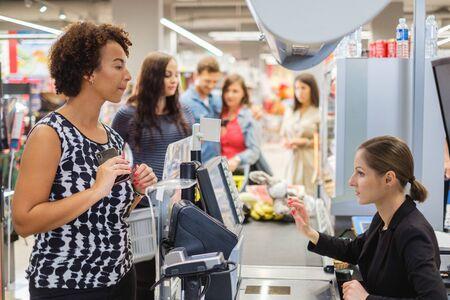 Black woman buying goods in a grocery store Foto de archivo - 138042062