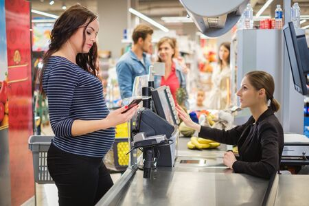 Pregnant woman buying goods in a grocery store Foto de archivo - 138041993