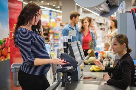 Pregnant woman buying goods in a grocery store Stok Fotoğraf