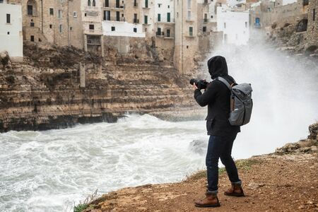 Photographer taking picture of a stormy sea in Polignano a Mare, Italy.