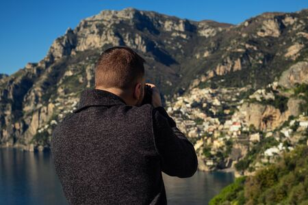 Man taking picture of Positano town, Italy