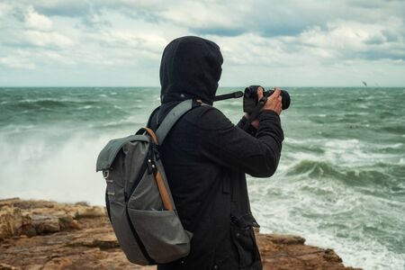 Photographer taking picture of a stormy sea