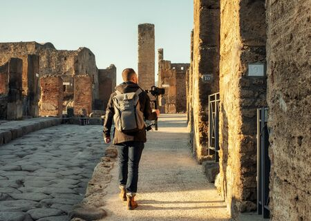 Videographer filming ruins of famous Pompeii city, Italy Banco de Imagens