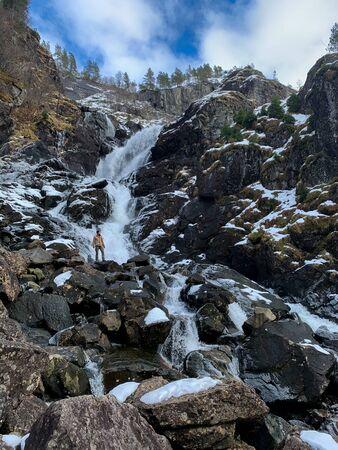 Man in front of Latefossen waterfall in winter, Norway Zdjęcie Seryjne