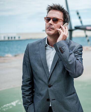 Businessman talking over the phone near private helicopter Zdjęcie Seryjne