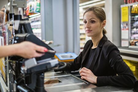Paying with ca smartphone in a grocery store Standard-Bild