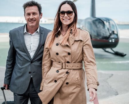 Young business couple near private helicopter Standard-Bild