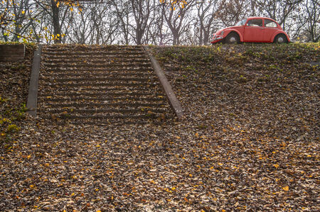 Abandoned old red car in a slope autumn meadow photo