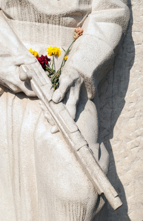 the liberator: Antifascist Stone monument sculpture dedicate to liberator soldier strewn with flowers Stock Photo