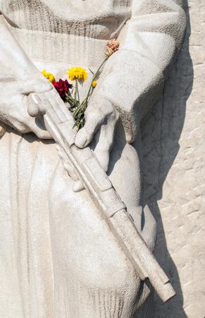liberator: Antifascist Stone monument sculpture dedicate to liberator soldier strewn with flowers Stock Photo