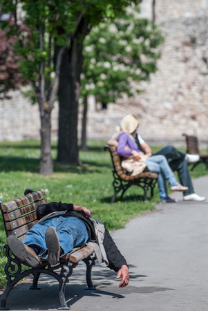 housing problems: Drinker sleeping on a park bench and a young couple in the background