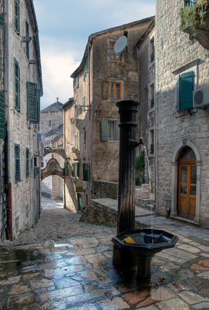 drinkable: Open drinking fountain in a small coastal town square with leaking tap (Kotor)