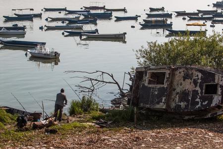 wrecks: Fisherman (rear) fishing in the marina next to the old wrecks