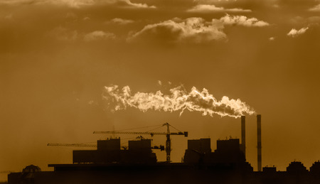 moody sky: Industrial area with city rooftops, moody sky and a lot of smoke Stock Photo