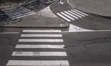 crossings: Traffic island with three pedestrian crossings photographed in low sunlight