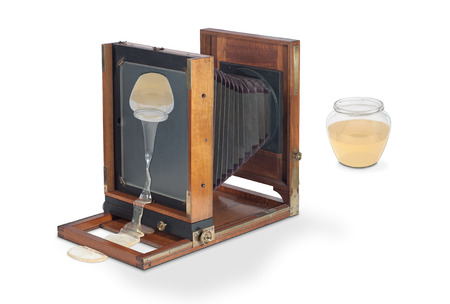 bellows: Old wooden largeformat studio photo camera with bellows and a reverse image of leaking honey jar on mat focus glass which defies the laws of physics, Isolated On White. The concept of camera obscura with intentional visual defect. Imaginary scene. Stock Photo
