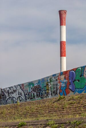 tall chimney: The old tall industrial chimney surrounded by a fence mottled with non-commercial graffiti