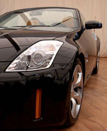 Black sports car headlight detail and alloy wheel     Stock Photo