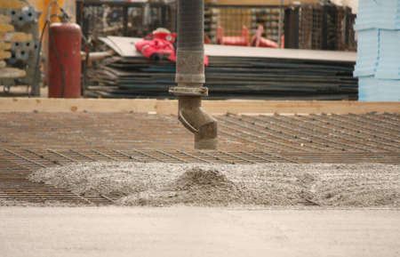 A pipe (hose) pouring out with liquid concrete in building site