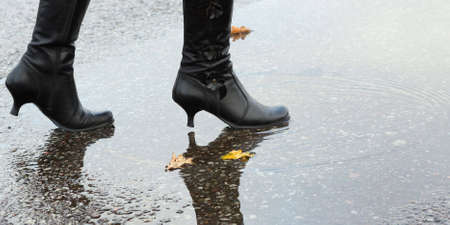 Woman stepping into a pool of water in autumn Stock Photo