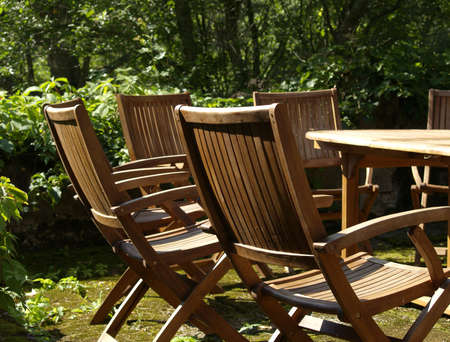 Wooden outdoor furniture: chairs and table, placed in garden photo
