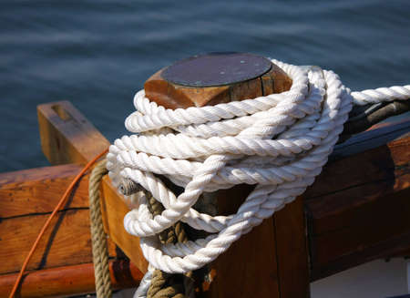 White boaters rope tied to dock boat photo