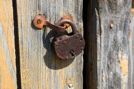 Old rusty padlock on the wooden door