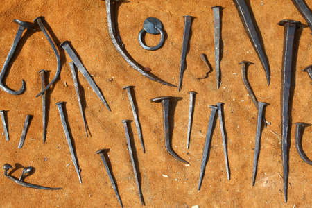 Different forged nails on the background of the leather Stock Photo