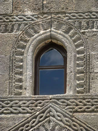 Window and stone wall with decorative stone carving. Lindos, Rhodes, Greece