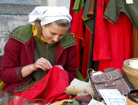 Tallinn, Estonia - June 5, 2010: A young girl in medieval clothes sells souvenirs. Tallinn Old Town Days