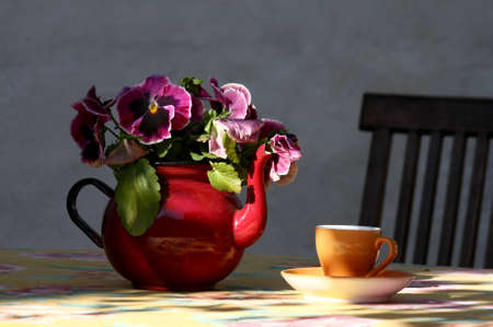 Teapot with flowers and cup on the table in an outdoor cafe. Tallinn, Estonia