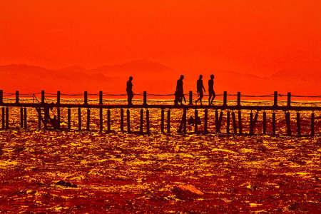 monte sinai: Mar ola sunset puente pier base de personas siluetas vacacionistas viajan turismo Monte Sina� Taba Egipto negro amarillo rojizo  Foto de archivo