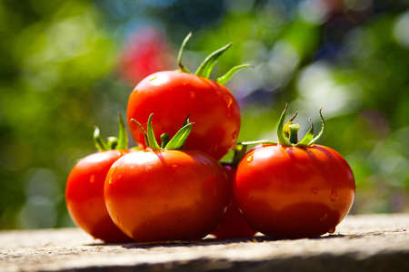 red tomatoes on a wooden table Stock Photo