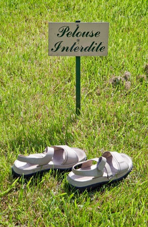 disobedience: prohibited lawn: pair of shoes on the lawn, a sign of disobedience Stock Photo