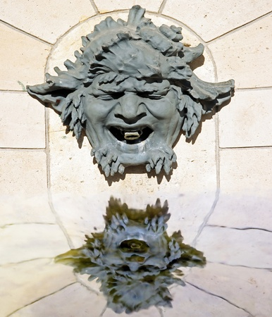 grotesque: grotesque, mask, and its reflection in water (a castle near Paris, France) Stock Photo