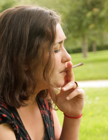 young woman smoking a rolled cigarette, portrait side photo