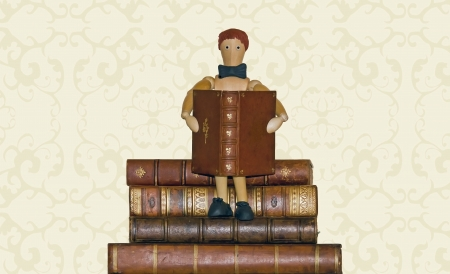 Reader, wooden snowman, sitting on pile of books Stock Photo - 15427100