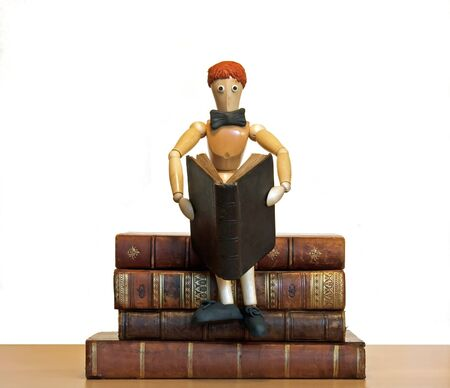 eacute: reader, wooden chap, sat on a pile of books